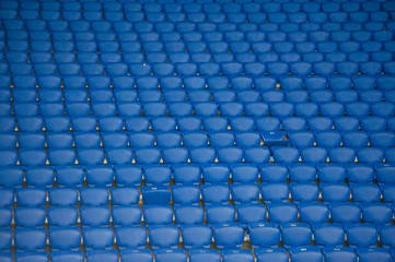 Blue empty seats at a football stadium. Yellow stairs with a number of sectors.