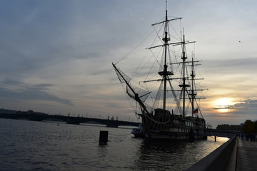 Old sailing ship at sunset. Panoramic view of Neva river .