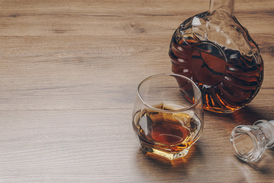 a glass of bourbon whiskey and a whiskey decanter on the wooden table