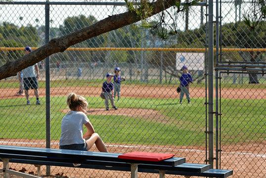 Girl on the bleachers watching little boys play t-ball.