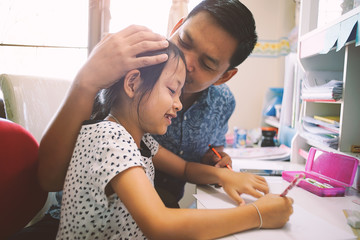 Young daughter and her father helping homework school project at home.
