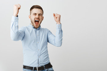 Yes we did it. Successful delighted and thrilled charming businessman in formal blue shirt yelling from excitement, joy raising fists to rejoice for successful deal celebrating victory over gray wall