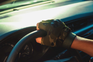 The hand of a man on a black steering wheel car. The man in the car. The driver of the vehicle. Rapid response team. Mobile group