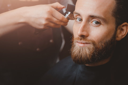 Barber shop. Man in barbershop chair, hairdresser styling his hair