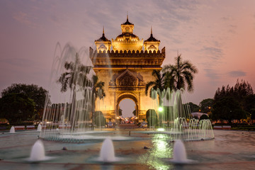 Fountain and palm trees in front of the lit Patuxai (Patuxay), Victory Gate or Gate of Triumph, war monument in Vientiane, Laos, at sunset.