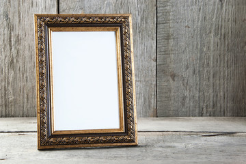 Empty picture frame on wooden background.