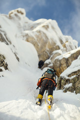 Climber ascent a rocky ridge covered with snow. Tilt-shift effect.