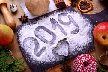 2019 inscription on a flour sprinkled board, Christmas cookies molds and ingredients for pastry