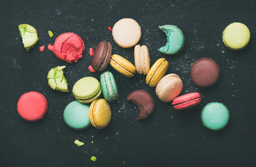 Flat-lay of sweet colorful French macaroon cookies variety over black background, top view