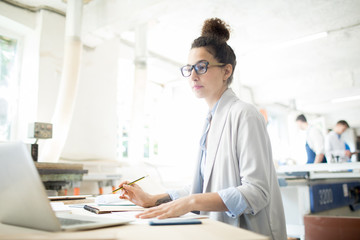 Young female worker in whitecoat looking at laptop display while reading online data by workplace