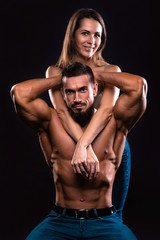 Fitness couple on a black background looking forward and smiling