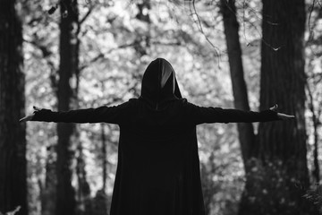 View from the back on a black witch in a mantle during ritual in a forest. Black and white moody photography. The concept of Halloween and witchcraft.