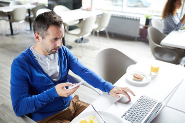 Busy young man in casualwear using modern gadgets by workplace during lunch break in office