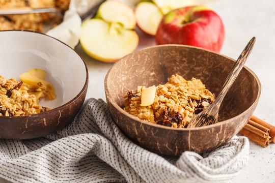 Autumn vegan apple oat crumble pie in coconut bowl.