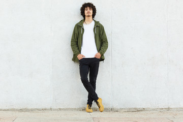 Full length shot of serious unshaven guy wears white t shirt, green anorak, black trousers and sneakes, keeps hands in pockets, has confident look directly at camera, isolated over white concrete wall