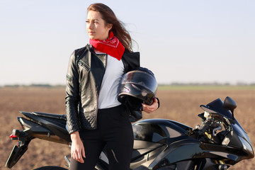Relaxed carefree female biker looks thoughtfully aside, carries helmet, dressed in black leather jacket, stands near motorbike, has stop in road, focused into distance. People, ride and morocycling