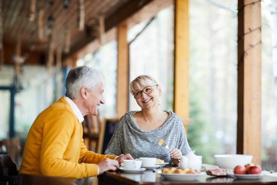 Happy blonde mature female talking to her husband while both having lunch in cafe