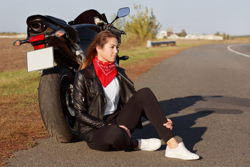 Sideways shot of pensive young experienced female biker wears leather jacket, white sneakers, sits near motorbike on asphalt, enjoys calm atmosphere in countryside. Risky sport and travelling