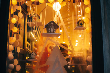 Delicious gingerbread cookie houses, stylish christmas decorations, garland lights in window in european city street. Festive decor and illumination in city center, winter holidays