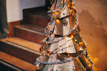Steampunk christmas tree. Creative steel tree with metal ornaments and branches, stylish christmas decorations and garland lights in european city street. Festive decor, winter holidays