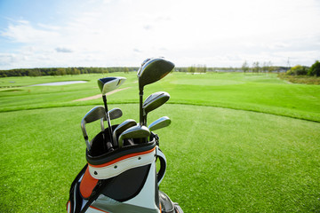 Bag with bunch of golf clubs and vast green field for playing golf on background