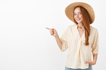 This way I show you. Portrait of charming happy and feminine redhead stylish woman enjoying summer day on beach in straw hat and trendy yellow blouse turning a camera and pointing left Wall mural