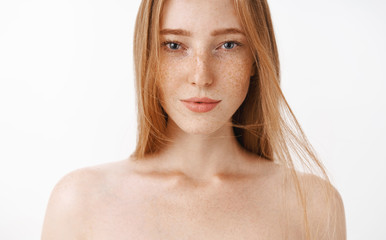 21875cc09 Close-up shot of attractive feminine naked redhead woman with freckles  posing over gray background