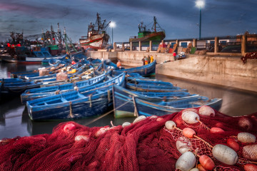 Morocco Essaouira harbor at night. Selective focus on the foreground red fish netting and floats. Background motion blur of colorful blue boats and seagulls in flight. Picturesque fishing village.