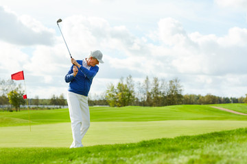 Active mature man going to hit ball by club while playing golf on large green field at leisure