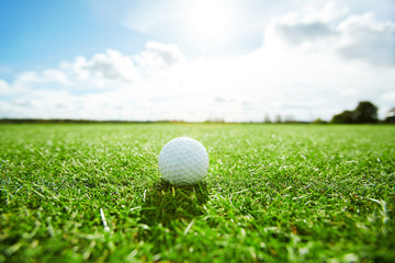 White golf ball laying on green grass of play field on sunny day with cloudy sky above