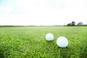 Two golf balls on green grass of vast play field in natural environment