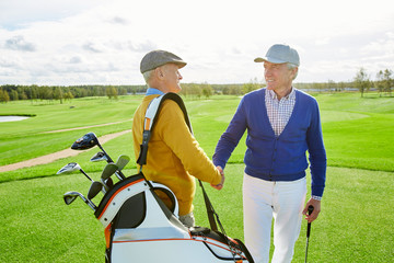 Two friendly mature golf players shaking hands while greeting one another before game