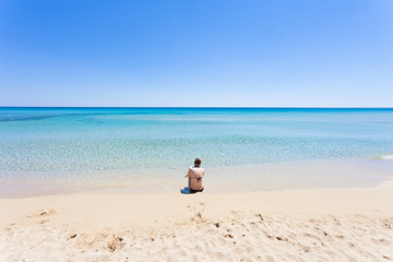 Lido Venere, Apulia - A young mother sitting on the beach looking towards the horizon