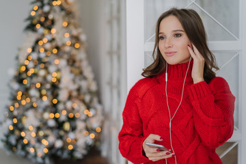 People, holidays and technology concept. Pretty woman uses mobile phone and earphones for listening music, stands at home against Christmas tree lights background with copy space for your text