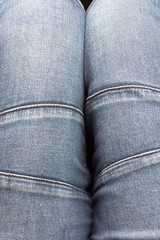 Top view of the jeans worn on the legs. Close-up, denim texture with seams
