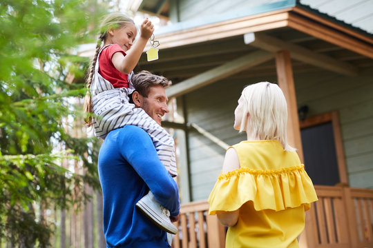 Young husband with daughter on shoulders and his wife talking outdoors by their new country house
