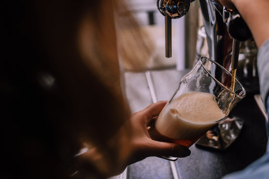 Girl pouring a pint of dark beer in a craft beer pub. Local pub. Shiny beer taps on the background. Bright sunny afternoon. Look from a shoulder