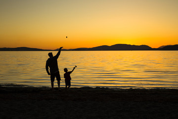 man and child playing at the seashore