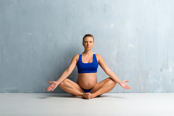 Blonde pregnant woman doing yoga