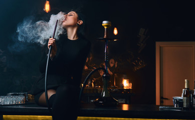 Sexy brunette girl in seductive black clothes smokes a hookah while sitting on counter in a nightclub or bar.