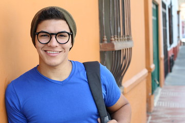 Handsome young hispanic male smiling outdoors