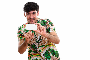 Studio shot of young happy Persian man smiling while taking pict