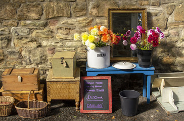 Antiques in street market infront of warm natural stone wall