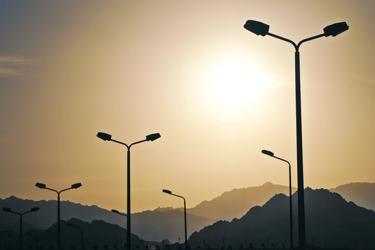 High-speed road highway with city lighting poles lamps. High mountains in the fog against the background, sunset, twilight, landscape, aerial perspective, cars