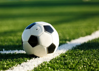 classical black and white football ball on the green grass of the field. Soccer game, training, hobby concept. with copy space