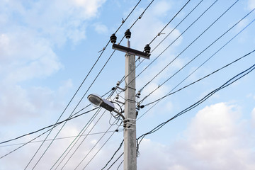 Lots of wires and cables and a street lamp with a blue sky background. power line. electric pole