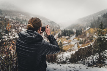 A man taking a photo in the mountains during an autumn snow storm.