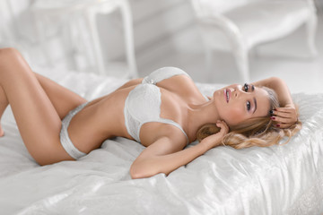 Sexy girl with gorgeous body in white lingerie on the bed