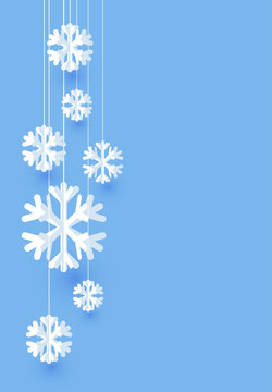 Blue Christmas card with white paper snowflakes.