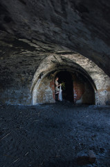 unusual wedding photo, the bride in a short seom dress in the catacombs